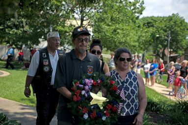 William Harris, left, and his wife, Jean Harris, carry a wreath with a gold star in remembrance of their son, Joshua, who died in Afghanistan in 2008, on May 28, during a Memorial Day Veterans ceremony at Veterans Park in Brookfield. | Alexa Rogals/Staff Photographer