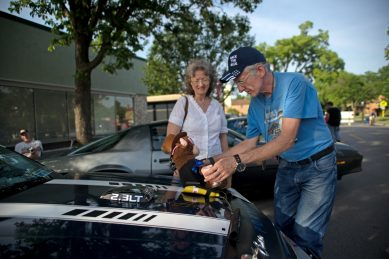 John Paida, of Cicero, and his sister Marlene Nowicki, of Berwyn, decorate Paida's car with a stuffed animal monkey on June 7, during the first monthly Cruise Night of the summer in downtown Riverside. | Alexa Rogals/Staff Photographer