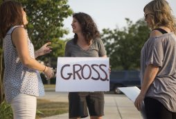 """Amy Jacksic, of Riverside, holds up a sign that says """"Gross"""" outside on Aug. 13, during a North Riverside Village board meeting at the Village Commons on Des Plaines Avenue. 
