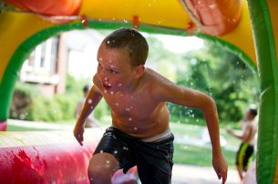 Aiden Burns scampers through the inflatable slip-and-slide during the 30th Annual Maplewood Road Block Party on Aug. 18 in Riverside. | Alexa Rogals/Staff Photographer