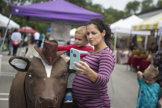Tammy Miller, of Brookfield, takes a selfie with her son, Sebastian, 2, in front of the Brookfield Restaurant - soon to be the Tony's Restaurant - cow at the Brookfield Farmers Market on Page 8. The cow will get a new paint job before going back to its longtime home on the roof at 8900 Ogden Ave.   Alexa Rogals/Staff Photographer