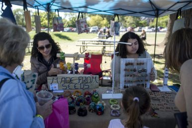 Geselle Cortez, left, and Ivana Valencia, both of Brookfield, talk with perspective buyers about their organic, hand made jewelry on Sept. 22, during the annual Fine Arts Festival at Kiwanis Park in Brookfield. | Alexa Rogals/Staff Photographer