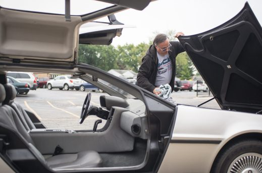 Rich Weissensel, of Brookfield, cleans up the front trunk of the De Lorean on Oct. 5, during the walkathon inside the gymnasium at Congress Park School in Brookfield. | Alexa Rogals/Staff Photographer