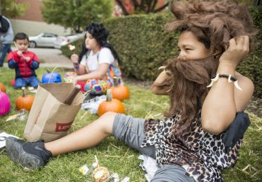 Sebastian Flores, 9, of Cicero, wears a caveman costume and enjoys eating his taffy apple during the annual Monsters on Mainstreet trick-or-treating event on Oct. 27.   ALEXA ROGALS/Staff Photographer