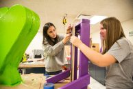 Ella Gomez, left, and Isabella O'Brien, both freshman, work on building a piece for the play Nov. 3, during dress rehearsals for Alice In Wonderland at Riverside Brookfield High School. | ALEXA ROGALS/Staff Photographer