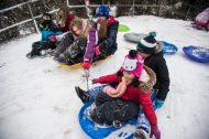 A group of kids hold onto each others sleds and ride down the hill together on Nov. 26, at the North Riverside Village Commons sledding hill on Des Plaines Avenue in North Riverside. | Alexa Rogals/Staff Photographer