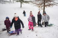 Children make their way back up the hill with their snowboards and sleds on Nov. 26, at the North Riverside Village Commons sledding hill on Des Plaines Avenue in North Riverside. | Alexa Rogals/Staff Photographer