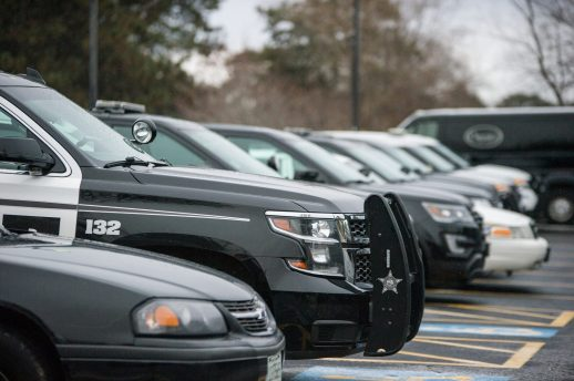 Dozens of law enforcement vehicles for different towns are seen parked in the parking lot on Jan. 2, at Woodlawn Cemetery in Forest Park. | ALEXA ROGALS/Staff Photographer