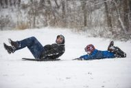 Noah Angarita, 8, of Riverside, slips off the sled as he and his dad, Edward, hit the bottom of the hill at Swan Pond Park in Riverside on Jan. 12. | Alexa Rogals/Staff Photographer