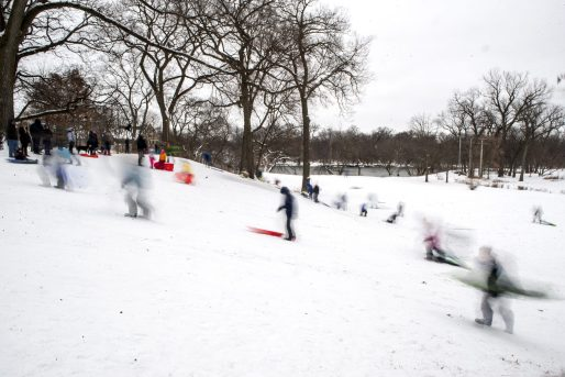 Kids and adults climb the hill after sledding down it on Jan. 19, at Swan Pond in Riverside. | ALEXA ROGALS/Staff Photographer
