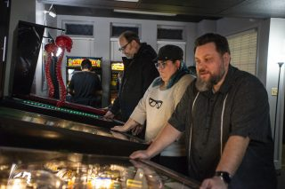 Guests play the new pinball games, from left, Predator, Alien and Godzilla on March 2, during the opening night of Galloping Ghost's Pinball Arcade on Ogden Avenue in Brookfield. | ALEXA ROGALS/Staff Photographer