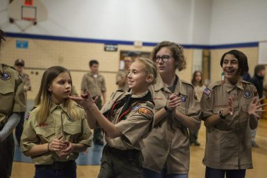 From left, Laura Geisert, 11, Ella Tamburello, 11, Kailey Fouts, 14, and Elaina Markus, 12, cheer for their scout leaders on Feb. 27, during an induction ceremony for the Boy Scouts of America Troop 90GT at Brook Park Elementary School in La Grange Park. | ALEXA ROGALS/Staff Photographer