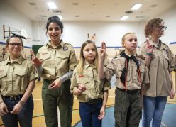 From left, McKenzie Monahan, 16, Joanna Vera, 16, Laura Geisert, 11, Ella Tamburello, 11, and Kailey Fouts, 14, hold up their hands in the Scouts Salute on Feb. 27, during an induction ceremony for the Boy Scouts of America Troop 90GT at Brook Park Elementary School in La Grange Park. | ALEXA ROGALS/Staff Photographer
