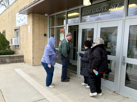 Mary Kalfas (second from right) and Joanne Schaeffer (far right) hand out palm cards to voters entering the Lincoln School in Brookfield on April 2. Schaeffer, who was a member of the losing Putting Students First slate, will see her 40-year tenure on the board come to an end. (Bob Skolnik | Contributor)