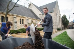Pastor Chris Honig shovels mulch into a wheelbarrow on April 22, at Ascension Lutheran Church on Nutall Road in Riverside. Church members (below) help shovel up mulch to put in the garden beds. | Alexa Rogals/Staff Photographer