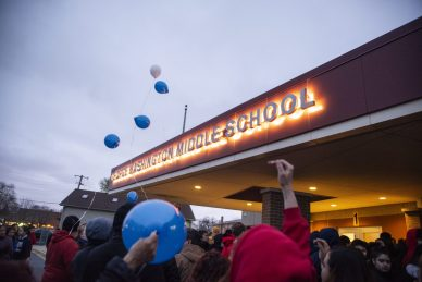 Community members release balloons on April 18, during a community prayer outside of the front entrance of George Washington Middle School in Lyons. | Alexa Rogals/Staff Photographer