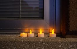 Candles are left on a window ledge on April 18, during a community prayer outside of the front entrance of George Washington Middle School. | ALEXA ROGALS/Staff Photographer