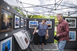 Attendees look through photos for sale in one of the booths on May 18, during the Riverside Arts Weekend, also known as RAW, at Guthrie Park in Riverside. | Alexa Rogals/Staff Photographer