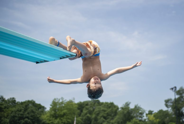 Kids do flips off of the high dive on Saturday, June 29, at the Riverside Swim Club in Riverside, Ill. | ALEXA ROGALS/Staff Photographer