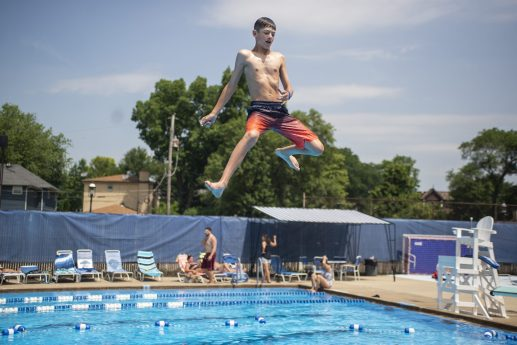 Guests jump off of the diving board on Saturday, June 29, at the Riverside Swim Club in Riverside, Ill. | ALEXA ROGALS/Staff Photographer