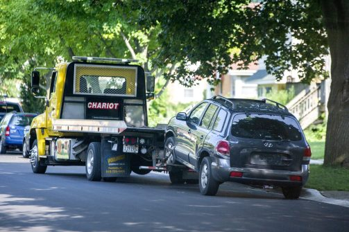Car recovered: A tow truck hauls away a gray Hyundai Santa Fe reportedly registered to robbery suspect Brian Shive from the 9000 block of 30th Street on July 25. A witness who chased one of the robbery suspects to the vehicle ripped the rear license plate from it and gave it to police. (Alexa Rogals/Staff Photographer)