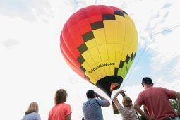 Ticket holders for the Riverside Hot Air Balloon Affair snap pictures of the first group being tethered 50 feet in the air on Saturday, Aug. 10, at Big Ball Park in Riverside, Ill. | SHANEL ROMAIN/Contributor