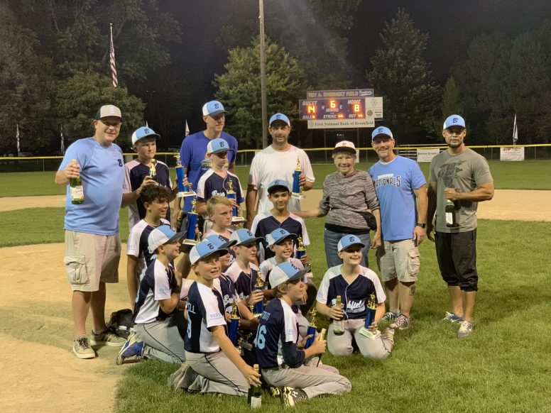 Brookfield celebrates its tourney win with some sparkling cider and a team photo with Audrey Overholt, wife of the late Roy Overholt, after whom the 56-year-old baseball tournament was named. | JAMES KAY/Staff