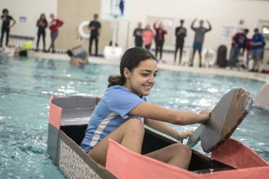 Madalynn Georgopoulos, a junior, is in control and above water as she paddles her team's boat across the pool.(Alex Rogals/Staff Photographer)