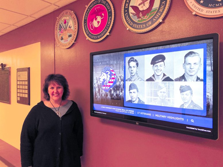 Jennifer Bialobok, community relations coordinator at LTHS, stands next to the interactive touchscreen where students and visitors can search the school's veterans' database, which is part of the new Wall of Honor area, which commemorates school alumni service in and for the Armed Forces, in the lower level of the North Campus in LaGrange. (Bob Uphues/Editor)