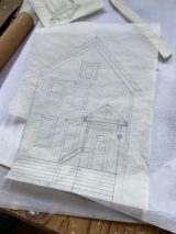 McCarthy sketches out buildings from photos and then places the paper on the clay, pricking holes in the paper to form the outline of her designs. (Bob Uphues/Editor)