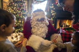 Santa hands a candy cane to a visitor at Irish Times in downtown Brookfield during the village's annual holiday celebration on Dec. 7.