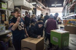 Volunteers pack up boxes of food for families in need on Dec. 22, 2019, at Twilight Party Rentals in Brookfield. | ALEX ROGALS/Staff Photographer