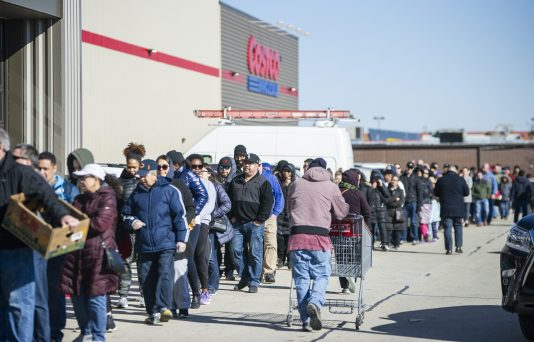 Shoppers queue up outside of Costco in North Riverside, from the front entrance to the warehouse's north end, on Friday, March 13 when panic buying began stripping grocery stores of canned goods, pasta, paper goods, water and cleaning products. (Alex Rogals/Staff Photographer)
