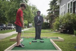 Killian Cwik, 9, lines up a putt as a cutout of Chicago Mayor Lori Lightfoot's meme-worthy glower stares back during the Brook Park Council's Summer Camp Progressive Putt Putt on one of the front lawn holes scattered throughout Brookfield and LaGrange Park on June 28. (Alex Rogals/Staff Photographer)