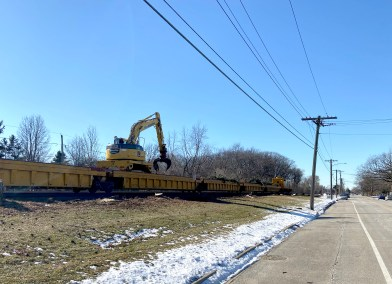 A backhoe mounted on a railcar lifts trunks and branches from fallen pine trees that lined the BNSF right-of-way along Brookfield Avenue in Brookfield for decades. Last week, the railroad began cutting down those trees as part of a right-of-way maintenance project stretching from downtown Chicago to Aurora. (Bob Uphues/Editor)