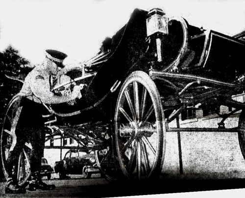 1957 - Photograph of an RCMP member polishing the Royal Carriage which Queen Elizabeth would ride in on her visit to Ottawa (Source of photo - Ric Hall's Photo Collection).