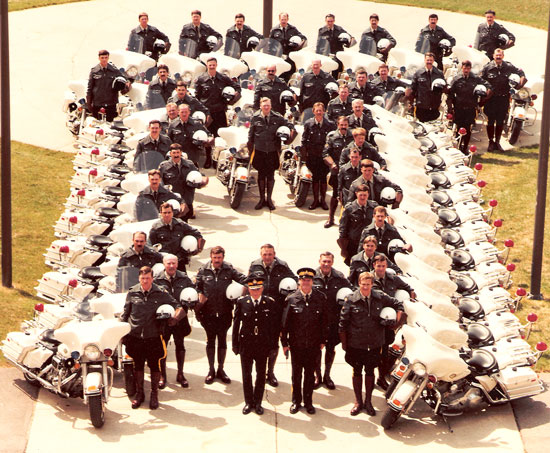 """1980s - Photograph of RCMP """"E"""" Division Traffic Section members with their motorcycles (Source of photo - Ric Hall's Photo Collection)."""