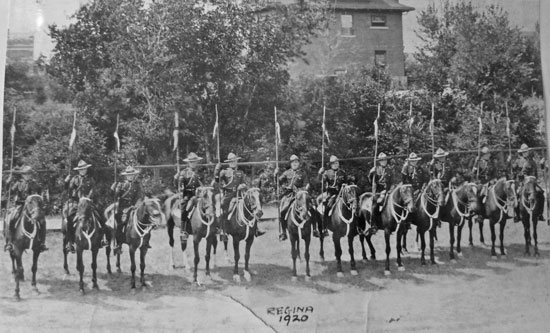 "1920: Photograph of RCMP members on horseback at ""Depot"" Division with ""A"" Block in the background (Source of photo - Ric Hall's Photo Collection)"