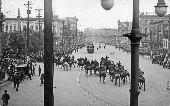 "Winnipeg General Strike: June 21, 1919 - Two troops of RCMP members regrouped and returend north.  Believing that the three dismounted men would be killed, the order was given to draw revolvers.  Turning left down William Street towards City Hall.  A warning volley was fired over the heads of the gathering.  When this failed to have effect, a second volley was fired low into the crowd which then began to disperse. (Source of photo - RCMP Historical Collections Unit - ""Depot"" Division)."