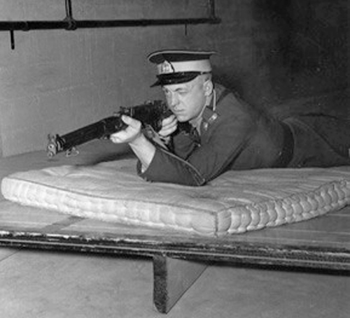 "1930s - Photograph of the  indoor rifle range in the basement of the gym at ""Depot"" Division.  Rifle being used is a .22 caliber. (Source of photo - Ric Hall's Photo Collection)."