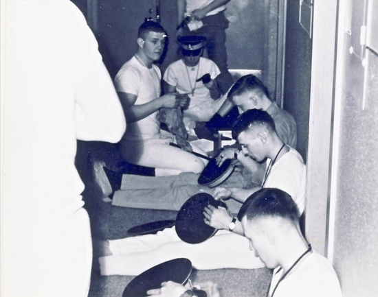 "A typical photograph of RCMP recruits clean and polishing their forge caps in preparation for the next day.  Photo was taken in one of the ""B"" Block dorms. (Source of photo - Ric Hall's Photo Collection)."
