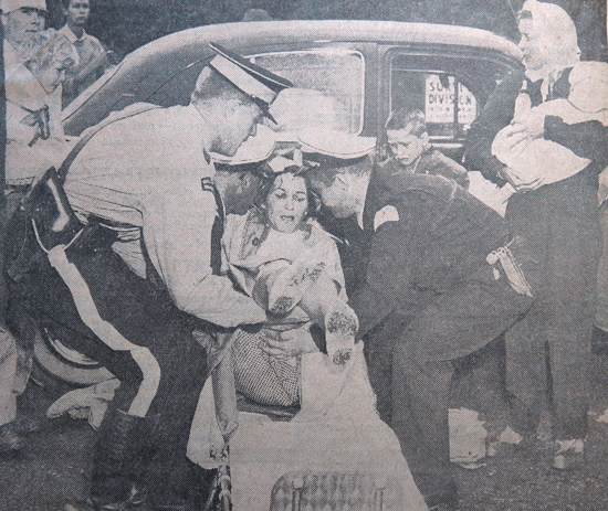 August 1962 - Photograph of a motor vehicle accident in Surrey with an RCMP member assisting with the placing of woman on a stretcher. (Source of photo - Barry Bradley's Newspaper Clipping Collection).
