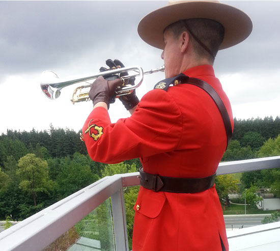 """June 10, 2014: Photograph of RCMP Constable playing """"Last Post"""" and """"Reveille"""" at the """"E"""" Division Headquarters in Surrey for the fallen three members killed in Moncton New Brunswick (photo taken by -Trish JOLAY in our MCMOSC unit)."""