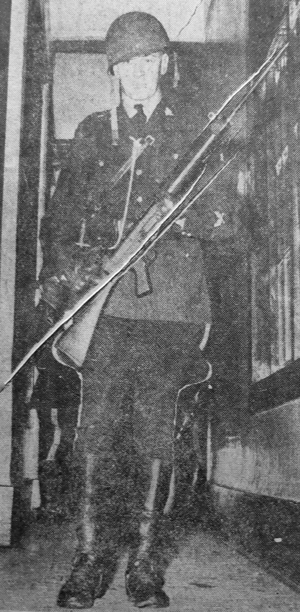 1963 - Photograph of an unknown RCMP member in uniform carrying an FN rifle while deployed to the June 19-20, 1963 BC Penitentiary riot.