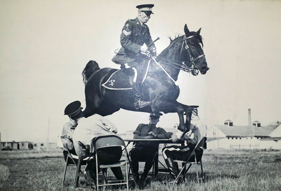 Photograph of a RCMP Riding Instructor demonstrating his skill in horsemanship to new recruits (Source of photo - Ric Hall's Photo Collection).