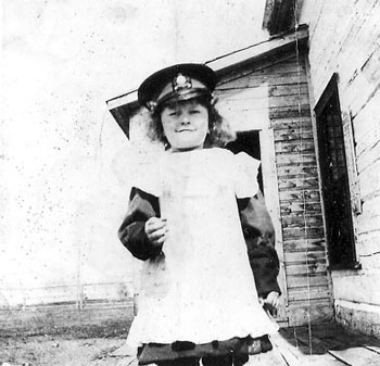 Photograph of a young daughter of a member trying on her dad's RCMP hat (Source of photo - Ric Hall's Photo Collection).