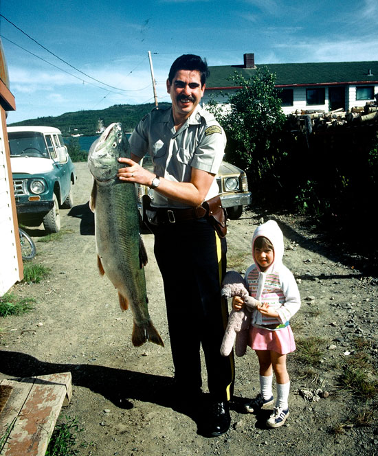 Photograph of Constable Peter Bird at Atlin Lake Detachment with his big fish catch (Source of photo - Ric Hall's Photo Collection).