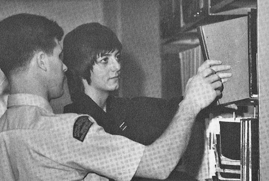"""Photograph of RCMP Troop #17 member: Barbara Wood being shown the Criminal Code case law volumes at """"Depot"""" Division (Source of photo - Ric Hall's Photo Collection)."""