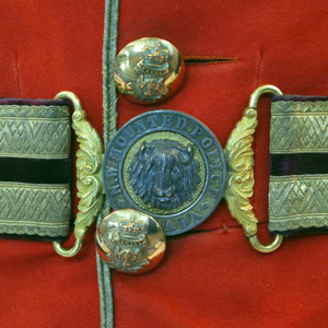 Photograph of a NWMP officer's belt buckle and red serge (Source of photo - Sheldon Boles).