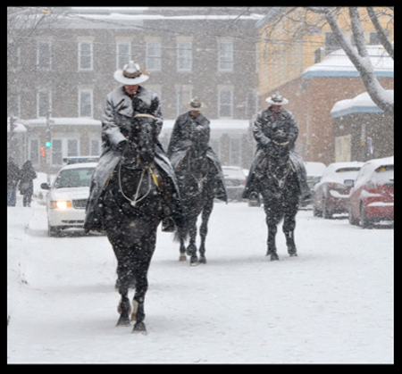 photograph of RCMP mounted members battling the snow. (Source of photo - Ric Hall's Photo Collection).
